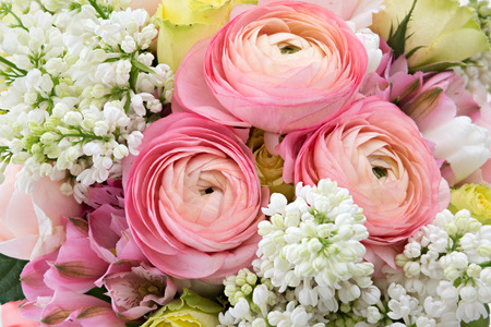buttercup flower: Spring flowers background with pink buttercups, yellow roses, white lilac and alstroemeria
