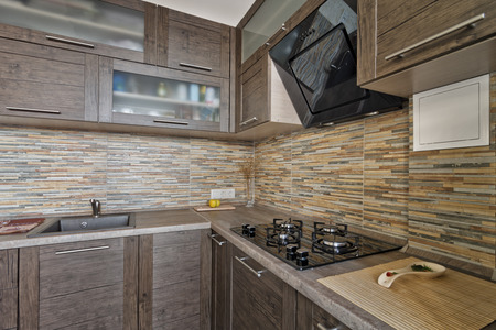 custom cabinet: Interior of small modern kitchen with wooden furniture Stock Photo