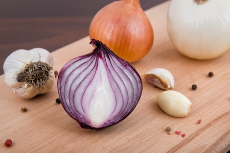 ajos: Red and white onion, garlic and spices on a wooden board