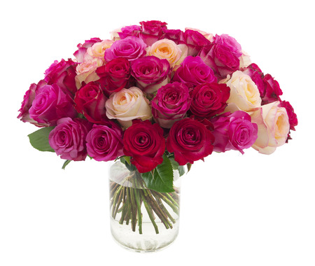 Many roses of red, pink and yellow colors in a vase isolated on white