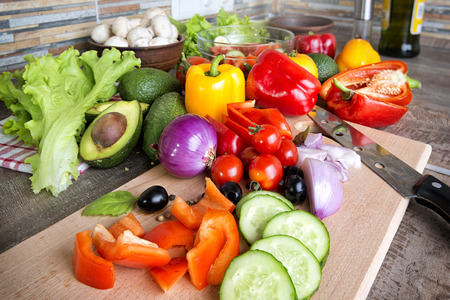 green pepper: Heap of cut and whole fresh vegetables for salad preparation on a kitchen table Stock Photo