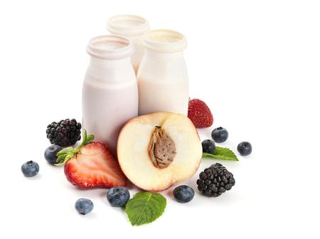 Yoghurt in plastic flessen met fruit en bessen op witte achtergrond