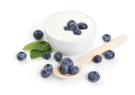 yogur: Yogur en un bol con arándanos en el fondo blanco