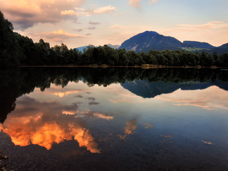 reflection: Sunset on a mountain lake with evening sun colored clouds and reflection