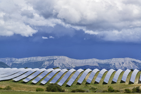 solar power plant: Solar panels lines in the field with big storm cloud in the sky Stock Photo