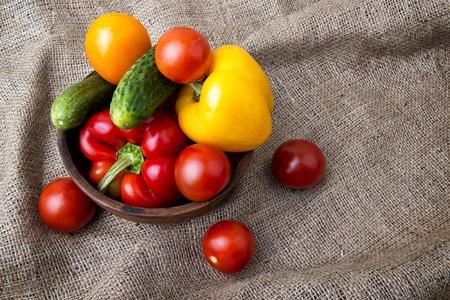 sackcloth: Fresh vegetables for salad in ceramic bowl on sackcloth background Stock Photo