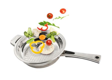 Verse gesneden groenten die vallen in de metalen pan op een witte achtergrond