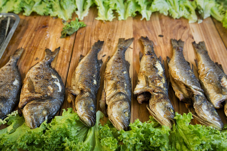 fest: Fried fish on a wooden table in a street food fest Stock Photo
