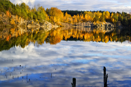 sky reflection: Fall time on a beautiful lake with rocky shore and sky reflection Stock Photo
