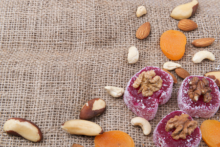 locum: Oriental sweets, nuts and dried fruits on a sackcloth background with copy space