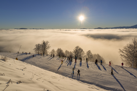 december sunrise: Bukovel, Ukraine, December 2016 � people skiing, watching and making selfie on a slope of the winter resort during beautiful sunrise over the clouds