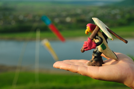 Funny plasticine hang glider pilot figure holding his wing ready to take off from human hand taken with macro lens