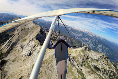 Self shot of brave extreme hang glider pilot flying above mount Krn in Slovenia taken with action camera Stock Photo