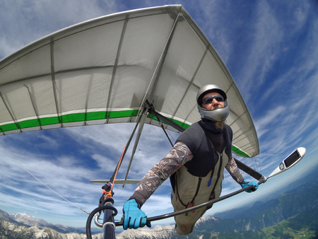 Selfie shot of brave extreme hang glider pilot soaring the thermal updrafts above mountains taken with action camera Stock Photo - 89770137