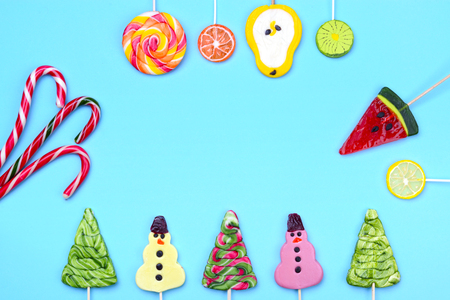Bright colorful creative layout for Christmas, New Year and winter holidays. Candy lollipops of funny snowman, Christmas tree, fruits, and candy cane. Place for the greeting text.