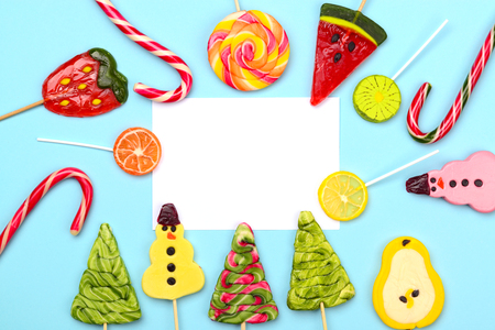 Colorful creative background for Christmas, New Year and winter holidays. Candy lollipops of funny snowman, Christmas tree, fruits, and candy cane. Place for the greeting text. Stock Photo