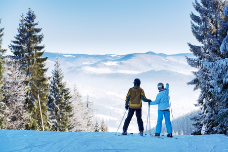 Couple of skiers watching beautiful landscape of a winter resort