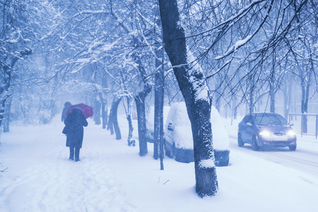 Unrecognizable people walking on the city street during heavy winter snowfall. Cars around are covered with snow