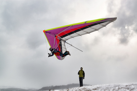 Kyiv, Ukraine. Pilot fly with a hang glider. Dramatic shot with strong wind and snow.