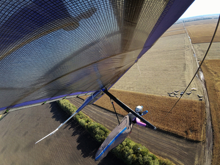 Selfie shot of brave extreme hang glider pilot flying  above autumn rural fields taken with action camera