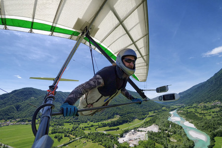 Selfie shot of brave extreme hang glider pilot soaring the thermal updrafts above alpine valley with emerald river taken with action camera Imagens
