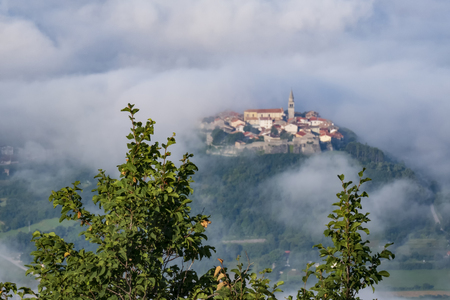 Ancient town with bell tower and old buildings on the top of a hill with clouds around. Unusual landscape of tourist destination in Istria, Croatia