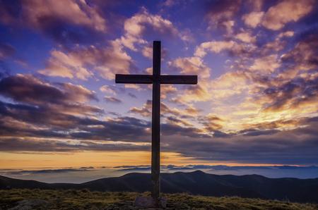Cross and beautiful pink sunrise. Symbol of hope. Фото со стока
