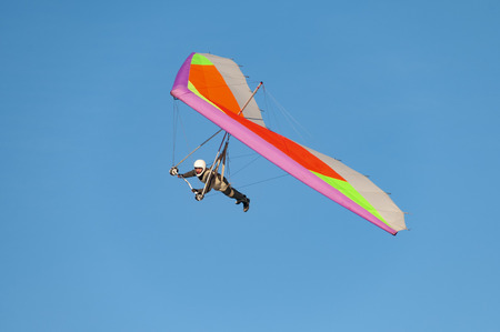Ukraine. Hang glider pilot fly his bright kite wing. Learning extreme sports