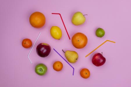 Fresh fruits and cocktail straws, flat lay. Juice ingredients in pink background. Apple, orange, tangerine, lemon, lime, pear
