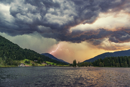 Dramatic thunderstorm with lightning and heavy rain at the lake