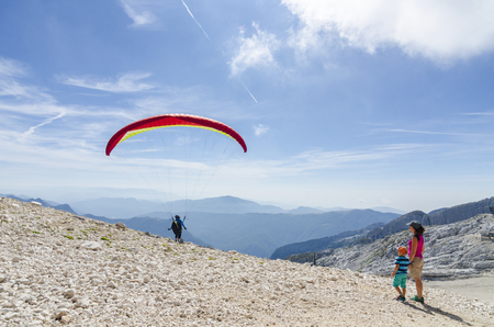 2018-09-12 Kanin, Slovenia. Mother and son watch the paraglider pilot take off high in the mountains. Extreme sport in summer 報道画像