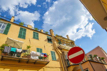 Vivid streets of italian town with vibrant blue sky, yellow walls, drying laundry and road sign. Imperia, Italy