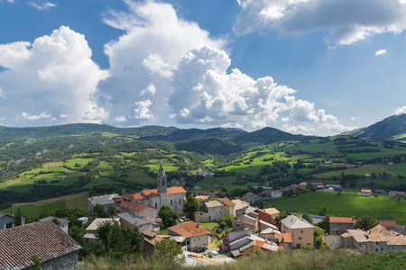 Green mountain valley in Provence, France. Green hills, small alpine town and blue sky. Beautiful summer landscape