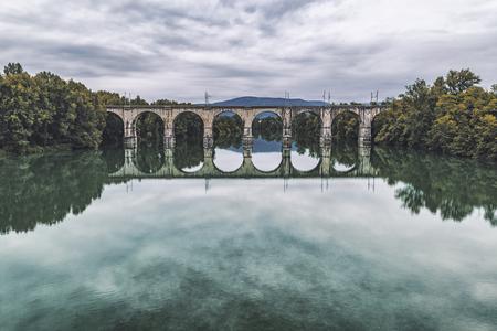 Vecchio ponte ad arco in pietra con riflesso nell'acqua. Colori vintage sbiaditi. Archivio Fotografico