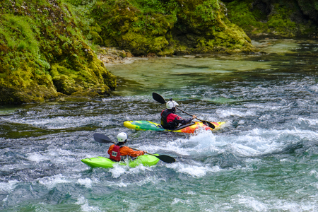 Two unrecognizable kayakers in the emerald water of Socha river in Slovenia.  Popular destination for active sports Imagens
