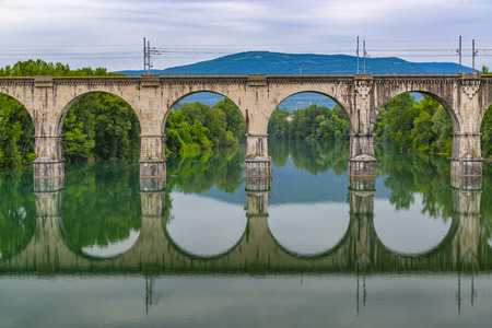 Old stone bridge reflection in the water. Architecture symmetry
