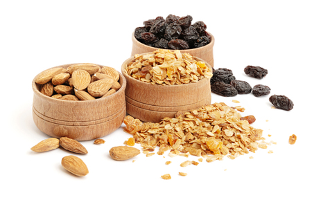 Granola, raisins and almonds in a wooden bowls on white background Banco de Imagens