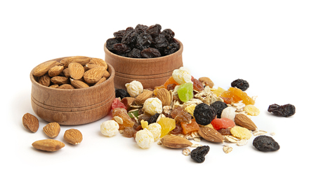 Heap of muesli and granola with dried fruits, almonds and raisins in wooden bowls