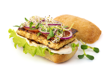 Opened vegan tofu burger with mushrooms and microgreens on white background with soft shadow