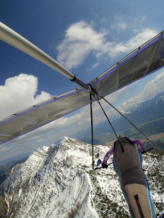 Brave pilot fly over mountain peak cobered by snow on a hang glider. Extreme aerial sport. Hang gliding