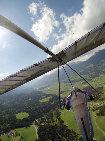 Hang glider pilot fly over green valley in Austria. Popular place for extreme sports