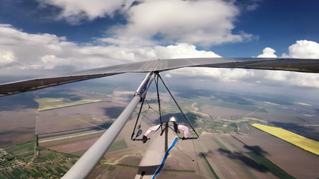 Hang glider pilot race between clouds on high altitude. Beauty of extreme sport