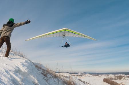 Un hombre que intenta coger el ala del ala delta volando. Diversión del deporte aéreo extremo