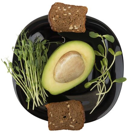 Healthy breakfast. Micro greens sprouts, avocado and bread on a black plate isolated on white background. Stok Fotoğraf