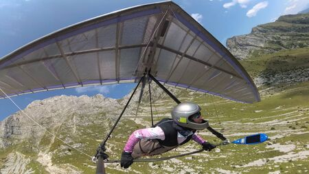 Hang glider pilot flies with his wing between high mountains.  Extreme sport in Soca valley, Slovenia