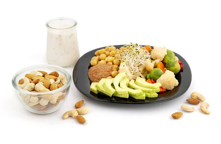 Healthy vegan meals with nuts, vegetables and chickpeas on white background