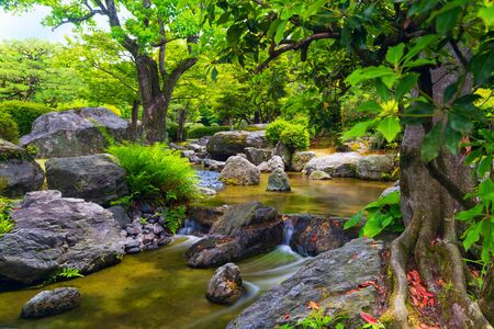 Morning scene in a Japanese garden with water stream, plants and stones