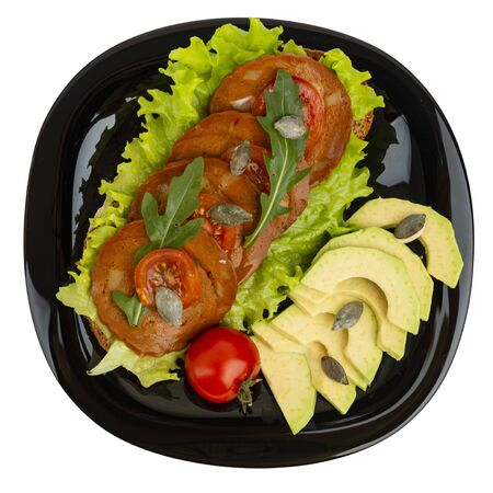 Healthy vegetarian food on a black plate isolated on white. 스톡 콘텐츠