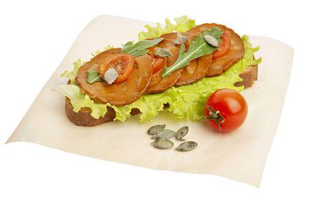 Vegan sandwich with seitan salami medallions rucola, pumpkin seeds and tomatoes