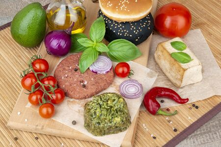 Vegan burgers, buns, tofu and vegetables on a wooden board ready for cooking Imagens